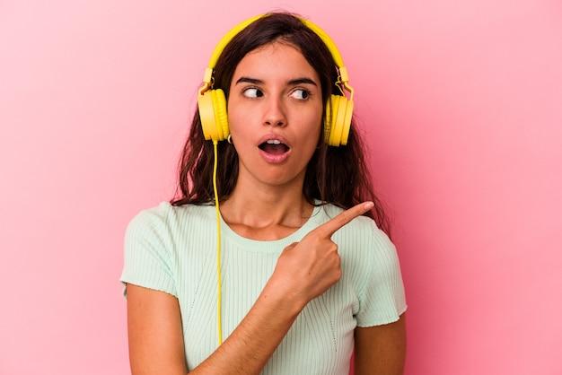 Jonge blanke vrouw die muziek luistert geïsoleerd op een roze achtergrond die naar de zijkant wijst