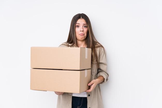 Jonge blanke vrouw die naar een nieuw huis verhuist, haalt schouders op en opent verwarde ogen.