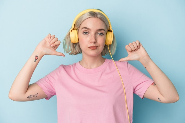 Jonge blanke vrouw die naar muziek luistert die op een blauwe achtergrond is geïsoleerd, voelt zich trots en zelfverzekerd, een voorbeeld om te volgen.