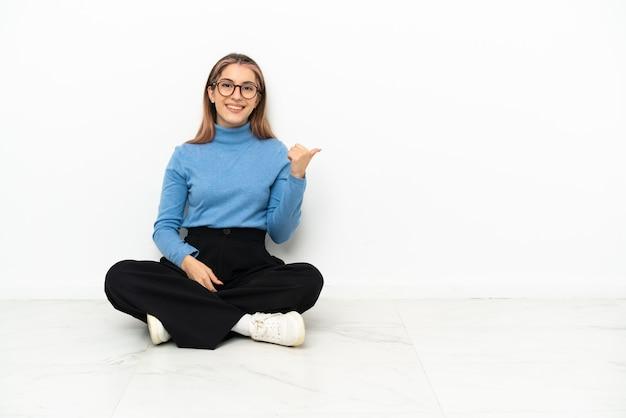 Jonge blanke vrouw die op de grond zit en naar de zijkant wijst om een product te presenteren