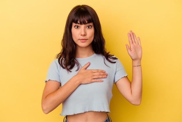 Jonge blanke vrouw die op gele achtergrond een eed aflegt, hand op de borst legt.