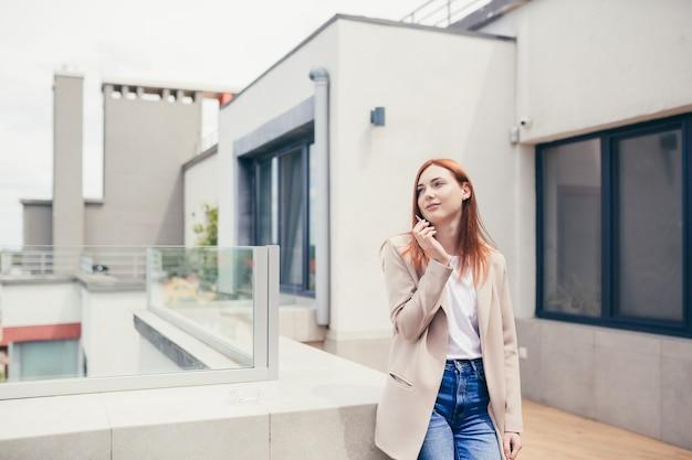 Jonge blanke vrouw die op het terras staat en marihuana rookt