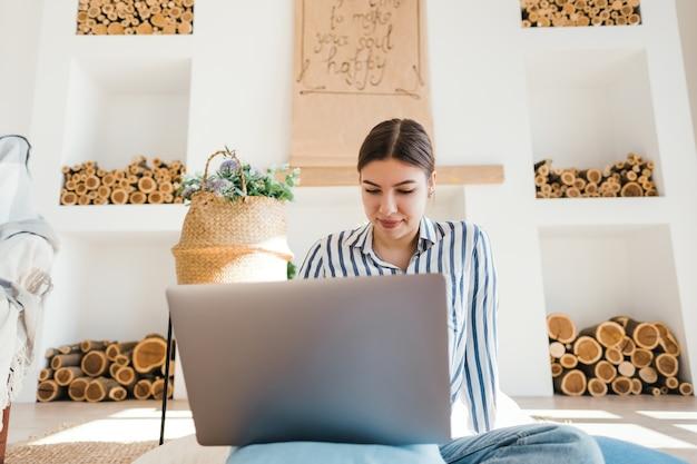 Jonge blanke vrouw die op laptop in gezellige woonkamer werkt, zittend op de vloer met kussens.