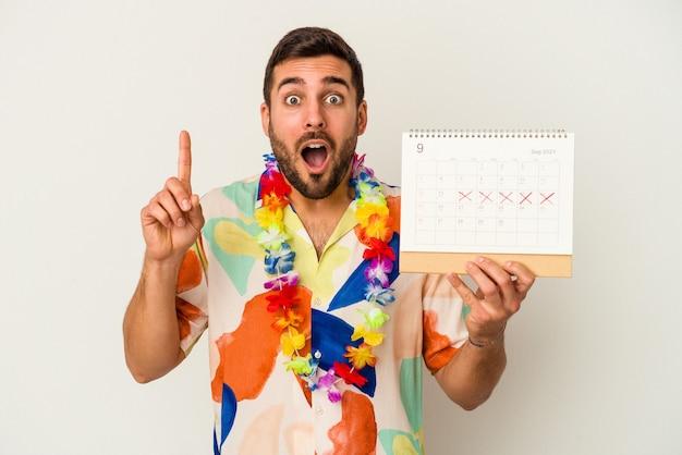Jonge blanke vrouw die op zijn vakantie wacht die een kalender houdt die op witte achtergrond wordt geïsoleerd die een idee, inspiratieconcept heeft.