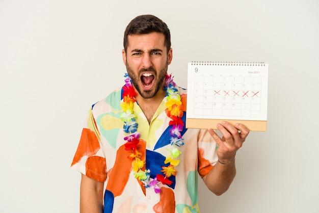 Jonge blanke vrouw die op zijn vakantie wacht die een kalender houdt die op witte muur wordt geïsoleerd die zeer boos en agressief gilt