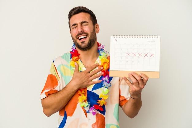 Jonge blanke vrouw die op zijn vakantie wacht met een kalender op een witte achtergrond lacht hardop terwijl ze de hand op de borst houdt.