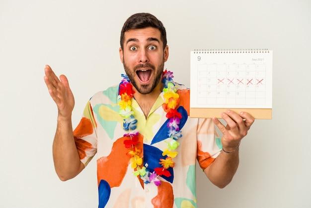 Jonge blanke vrouw die op zijn vakanties wacht die een kalender houdt die op witte achtergrond wordt geïsoleerd die een aangename verrassing ontvangt, opgewekt en handen opheft.