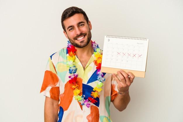 Jonge blanke vrouw die op zijn vakanties wacht die een kalender houdt die op witte achtergrond wordt geïsoleerd gelukkig, glimlachend en vrolijk.