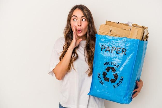 Jonge blanke vrouw die papier recyclet dat op een witte achtergrond wordt geïsoleerd, zegt een geheim heet remnieuws en kijkt opzij