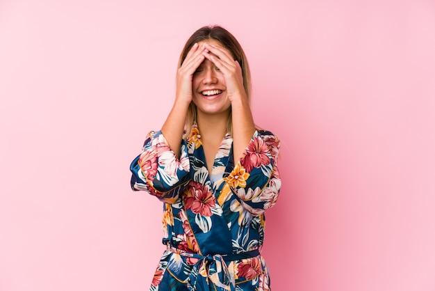 Jonge blanke vrouw die pyjama's draagt, bedekt ogen met handen, glimlacht in het algemeen wachtend op een verrassing.