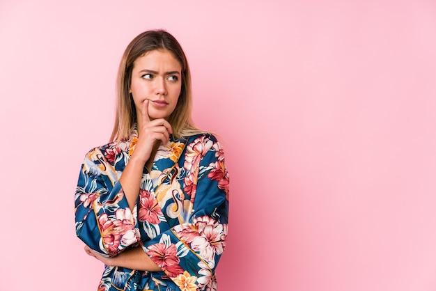 Jonge blanke vrouw die pyjama's draagt die zijwaarts kijkt met een twijfelachtige en sceptische uitdrukking.
