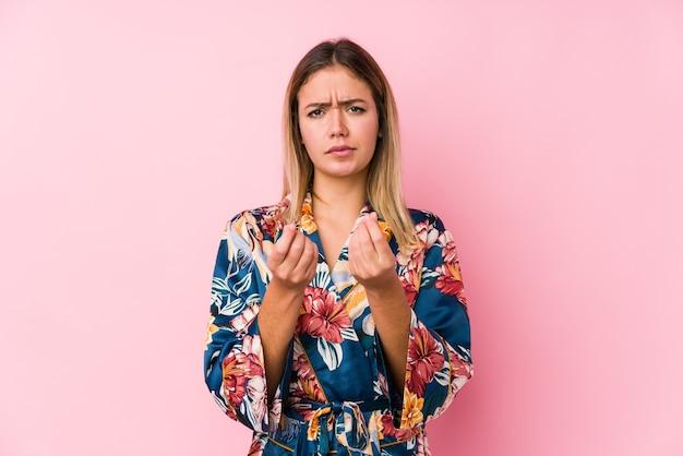 Jonge blanke vrouw die pyjama's draagt en laat zien dat ze geen geld heeft.