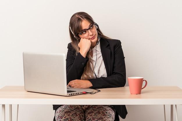 Jonge blanke vrouw die telewerken doet geïsoleerd op een witte achtergrond die zich verdrietig en peinzend voelt, kijkend naar kopieerruimte.