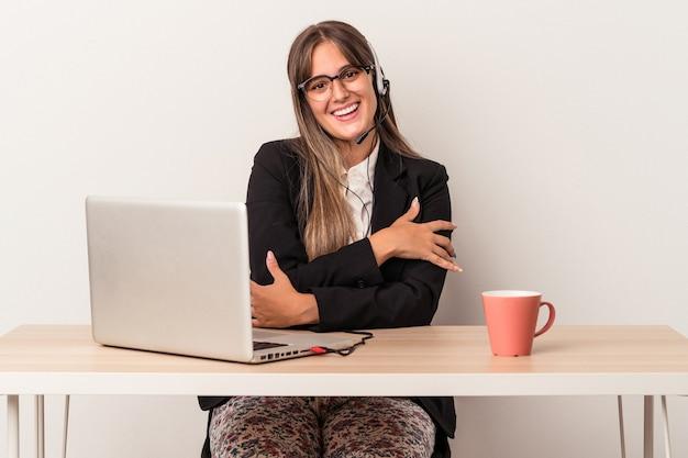 Jonge blanke vrouw die telewerken doet geïsoleerd op een witte achtergrond die zich zelfverzekerd voelt, armen met vastberadenheid kruisen.