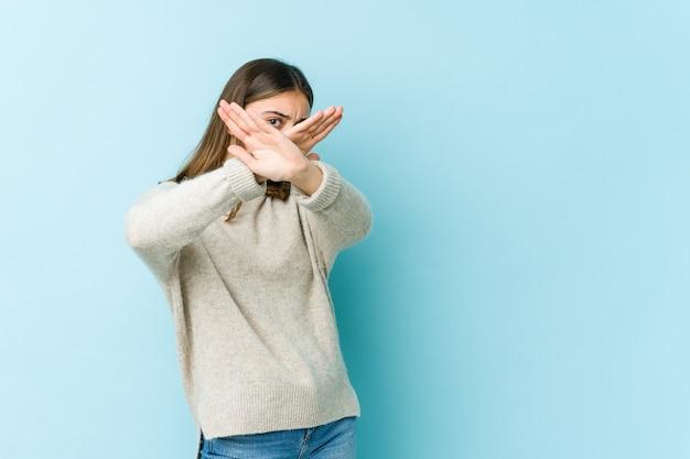 Jonge blanke vrouw die twee armen gekruist, ontkenningsconcept houdt.