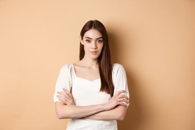 Jonge blanke vrouw die vastberaden en zelfverzekerd kijkt, staand met gekruiste armen, glimlachend naar de camera, gekleed in witte jurk, beige achtergrond.