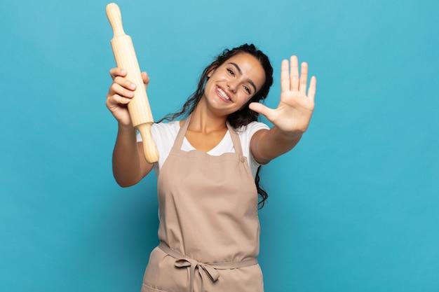 Jonge blanke vrouw die vriendelijk glimlacht en kijkt, nummer vijf of vijfde met vooruit hand toont, aftellend
