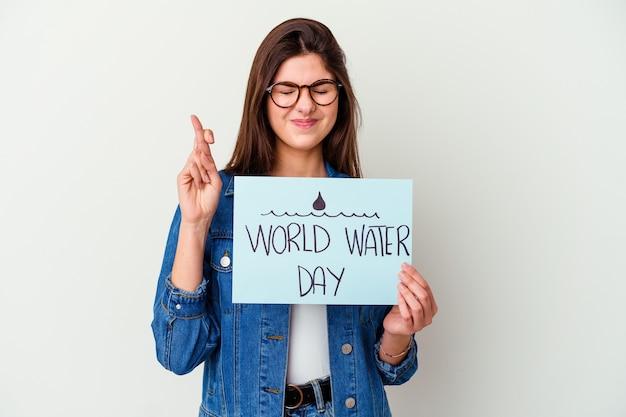 Jonge blanke vrouw die wereldwaterdag viert die op roze wordt geïsoleerd, voelt zich trots en zelfverzekerd, voorbeeld om te volgen.