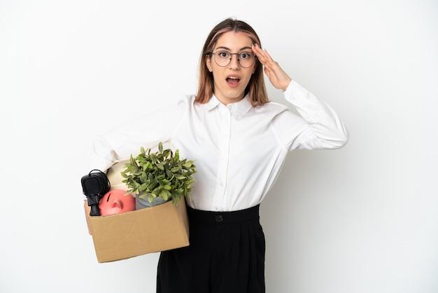 Jonge blanke vrouw die zich in een nieuw huis onder de dozen beweegt die op wit worden geïsoleerd met verrassingsuitdrukking