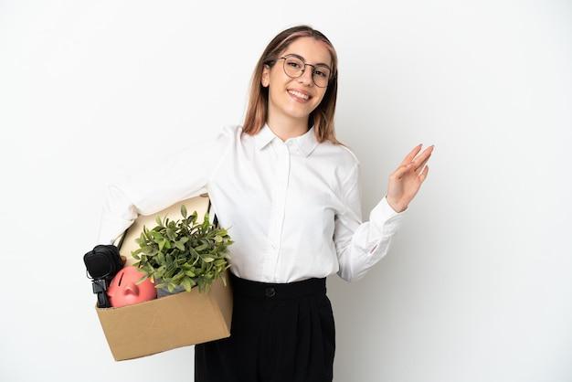 Jonge blanke vrouw die zich in een nieuw huis onder geïsoleerde dozen beweegt