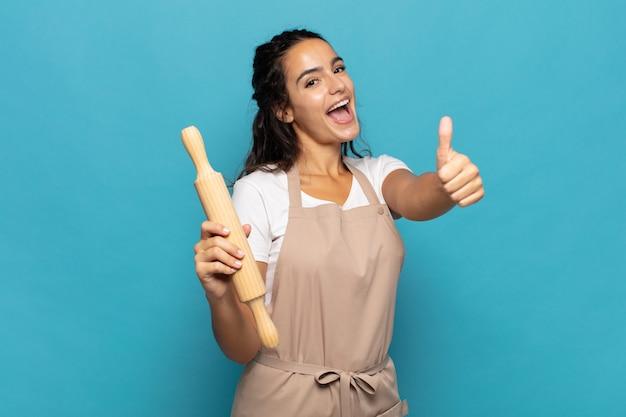Jonge blanke vrouw die zich trots, zorgeloos, zelfverzekerd en gelukkig voelt en positief glimlacht met omhoog duimen