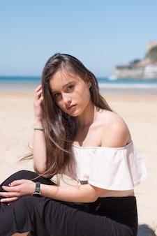 Jonge blanke vrouw die zich voordeed op het strand