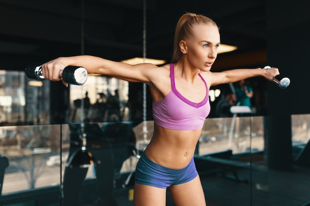 Jonge blanke vrouw doet oefening met halters tijdens het trainen van wapens in de sportschool