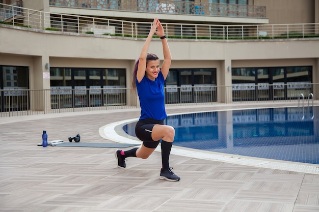 Jonge blanke vrouw doet oefeningen buiten naast het zwembad sport in pandemische tijd