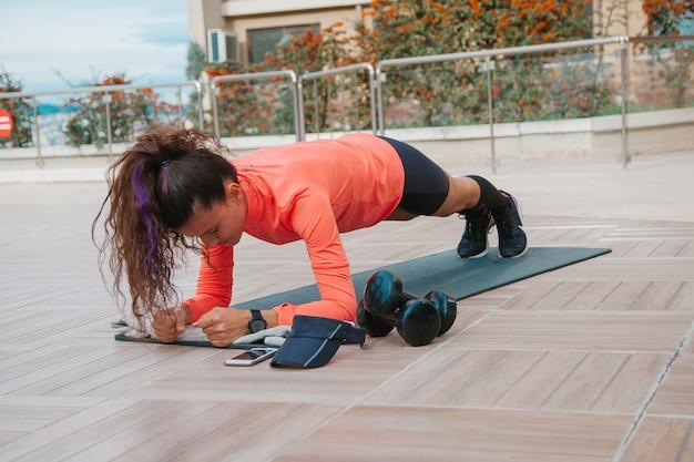 Jonge blanke vrouw doet plankoefeningen buiten sport in pandemische tijd yoga concept