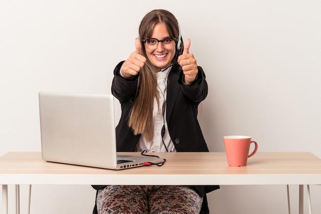 Jonge blanke vrouw doet telewerken geïsoleerd op een witte achtergrond met thumbs ups, cheers over iets, ondersteuning en respect concept.