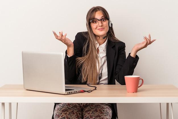 Jonge blanke vrouw doet telewerken geïsoleerd op een witte achtergrond twijfelen en schouders ophalen in ondervraging gebaar.