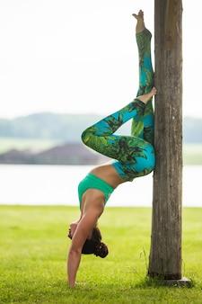 Jonge blanke vrouw doet yoga oefeningen in zomer stadspark