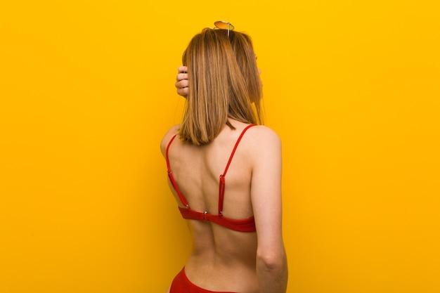 Jonge blanke vrouw draagt bikini en zonnebril van achteren na te denken over iets.