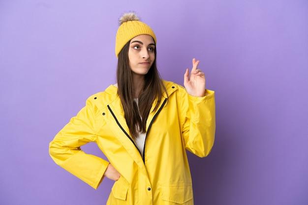 Jonge blanke vrouw draagt een regenbestendige jas geïsoleerd op een paarse achtergrond met vingers die elkaar kruisen en het beste wensen