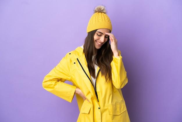 Jonge blanke vrouw draagt een regendichte jas geïsoleerd op een paarse achtergrond lachend