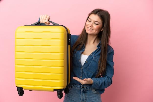 Jonge blanke vrouw geïsoleerd in vakantie met reiskoffer