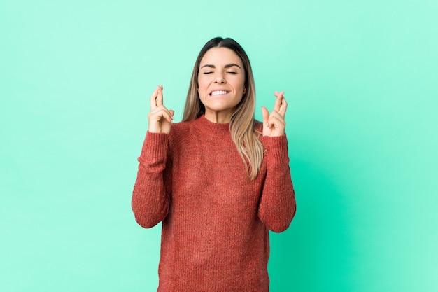 Jonge blanke vrouw geïsoleerd kruising vingers voor het hebben van geluk