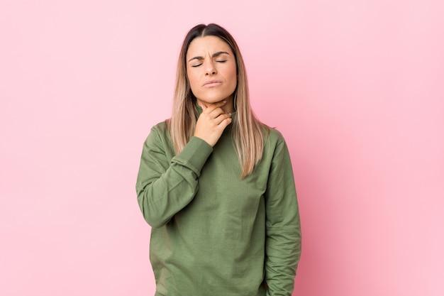 Jonge blanke vrouw geïsoleerd lijdt pijn in de keel als gevolg van een virus of infectie.
