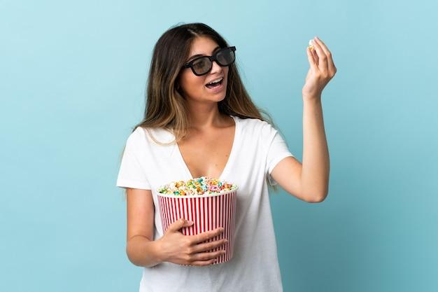 Jonge blanke vrouw geïsoleerd met 3d-bril en met een grote emmer popcorn