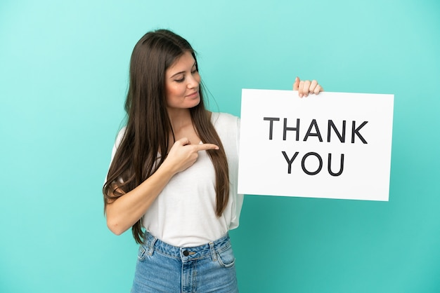 Jonge blanke vrouw geïsoleerd met een bordje met de tekst bedankt en erop wijzend
