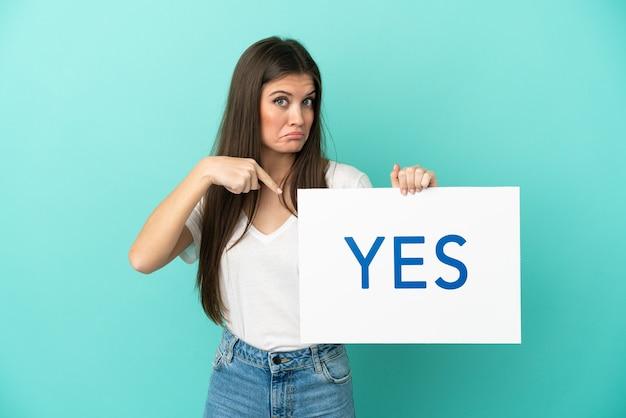 Jonge blanke vrouw geïsoleerd met een bordje met de tekst ja en erop wijzend