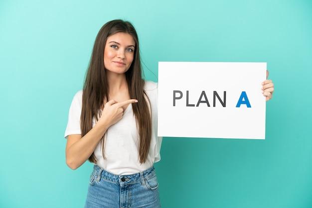 Jonge blanke vrouw geïsoleerd met een bordje met het bericht plan a en erop wijzend