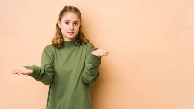 Jonge blanke vrouw geïsoleerd op beige maakt schaal met armen, voelt zich gelukkig en zelfverzekerd.