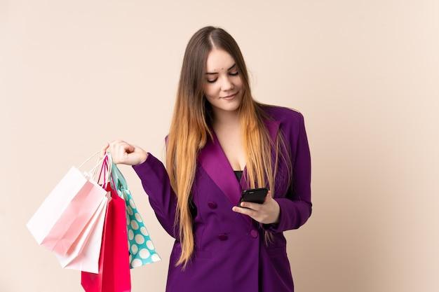 Jonge blanke vrouw geïsoleerd op beige muur boodschappentassen houden en het schrijven van een bericht met haar mobiele telefoon naar een vriend