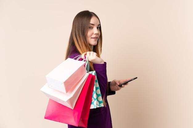 Jonge blanke vrouw geïsoleerd op beige muur met boodschappentassen en een mobiele telefoon