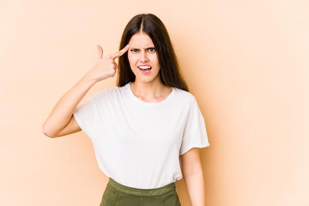 Jonge blanke vrouw geïsoleerd op beige muur met een teleurstelling gebaar met wijsvinger.