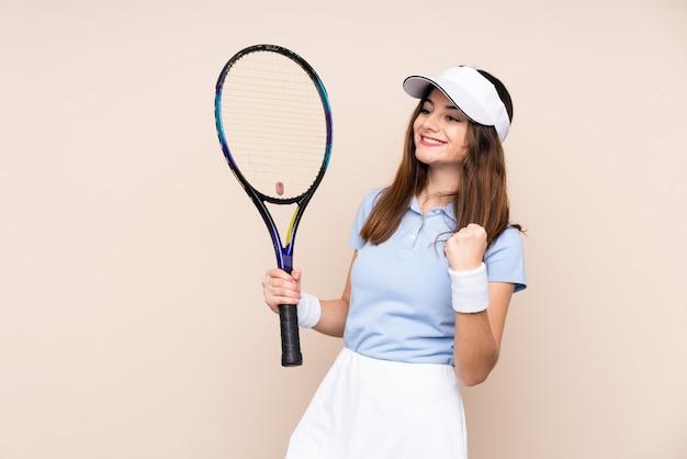 Jonge blanke vrouw geïsoleerd op beige muur tennissen en het vieren van een overwinning