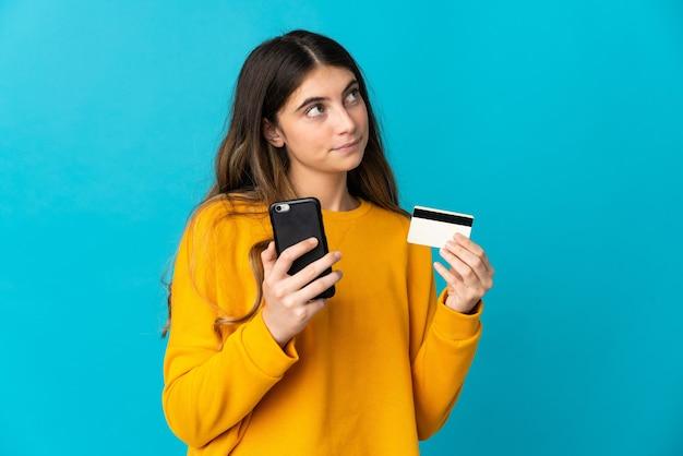 Jonge blanke vrouw geïsoleerd op blauw kopen met de mobiele telefoon met een creditcard tijdens het denken