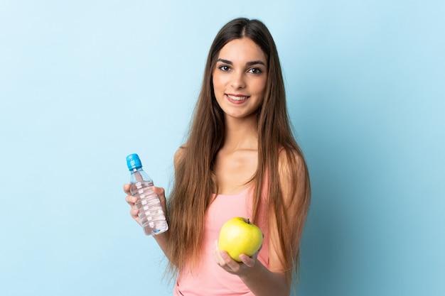 Jonge blanke vrouw geïsoleerd op blauw met een appel en met een fles water