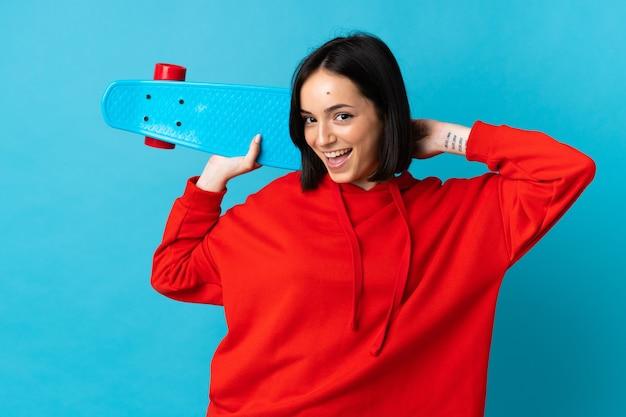 Jonge blanke vrouw geïsoleerd op blauw met een skate